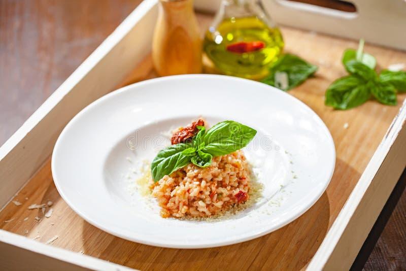 意大利煨饭用各式各样的蕃茄和雀跃在白色板材 库存照片