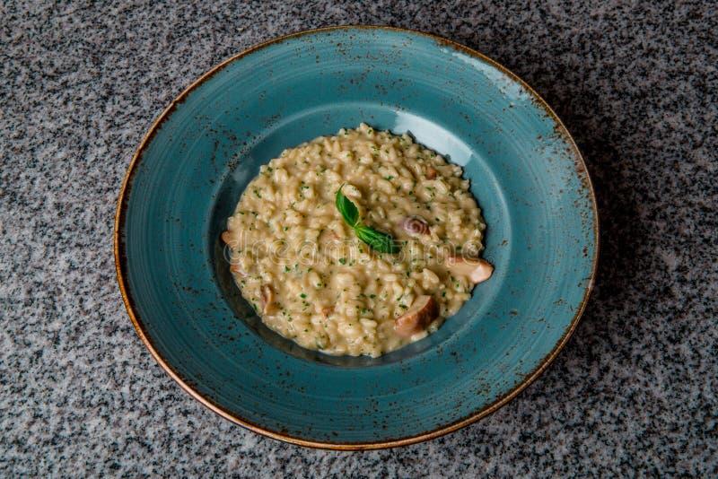 意大利煨饭用在一块绿色板材的蘑菇 库存图片