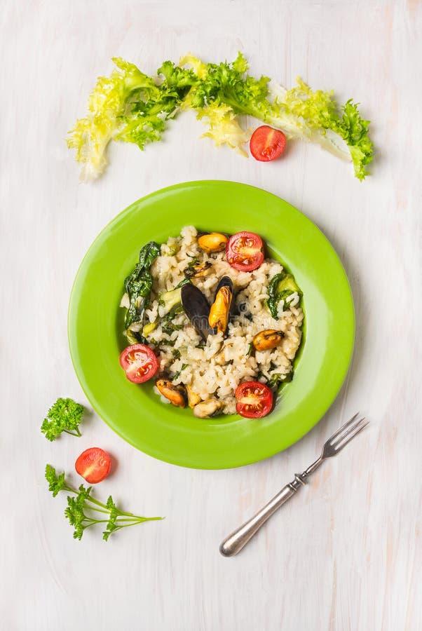 意大利煨饭用淡菜和绿色莴苣在一块板材在白色木 免版税库存照片