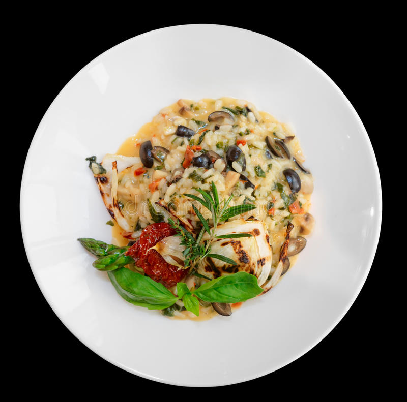 意大利煨饭用蕃茄和草本在板材,隔绝在黑色 图库摄影