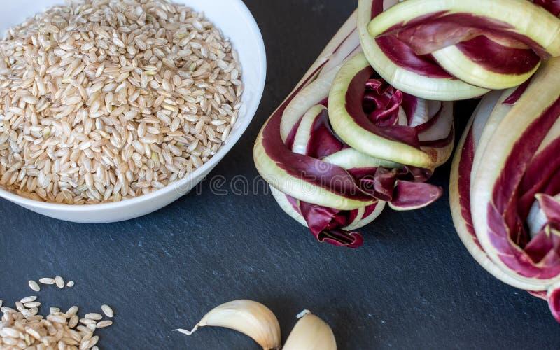 意大利煨饭的成份与特雷维索拉迪基奥,糙米,在板岩桌上的大蒜 免版税图库摄影