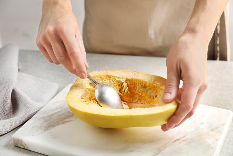 意大利粉南瓜妇女刮的骨肉与匙子的在桌上 图库摄影