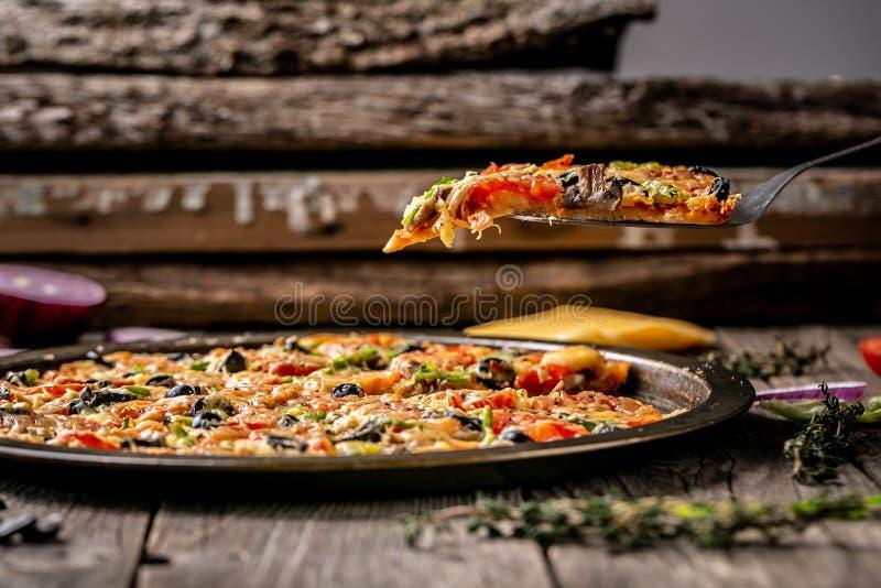 意大利自创比萨用乳酪和蕃茄在一张土气木桌上 餐馆或比萨店的海报 Copyspace 免版税库存照片