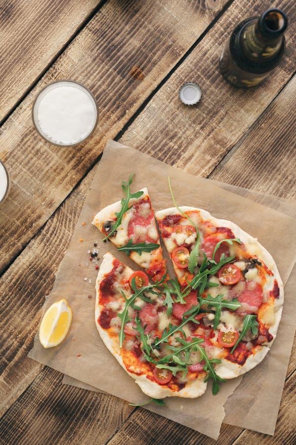 意大利自创薄饼用在土气木桌上的低度黄啤酒 免版税库存图片