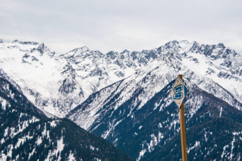 意大利阿尔卑斯,旅游标志雪靴,雪球拍 在背景的积雪覆盖的山 免版税库存图片