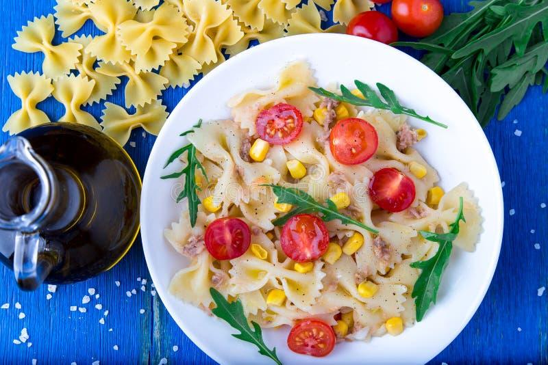 意大利面制色拉用在蓝色木背景的蕃茄樱桃、金枪鱼、玉米和芝麻菜 顶视图 库存图片