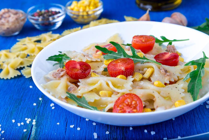 意大利面制色拉用蕃茄樱桃、金枪鱼、玉米和芝麻菜 关闭 免版税图库摄影