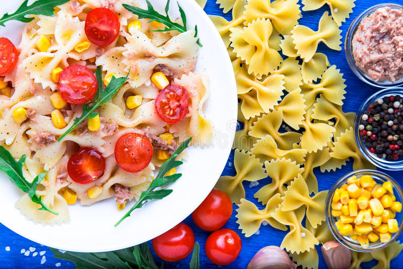 意大利面制色拉用蕃茄樱桃、金枪鱼、玉米和芝麻菜 顶视图 成份 免版税图库摄影