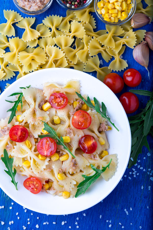 意大利面制色拉用蕃茄樱桃、金枪鱼、玉米和芝麻菜 顶视图 免版税库存图片