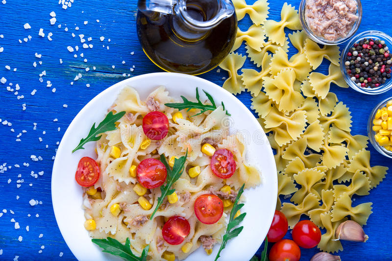 意大利面制色拉用蕃茄樱桃、金枪鱼、玉米和芝麻菜 顶视图 库存图片