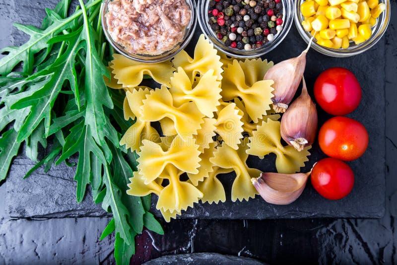 意大利面制色拉的成份在板岩板材用蕃茄樱桃、金枪鱼、玉米和芝麻菜 顶视图 烹调意大利语的食品成分 免版税图库摄影
