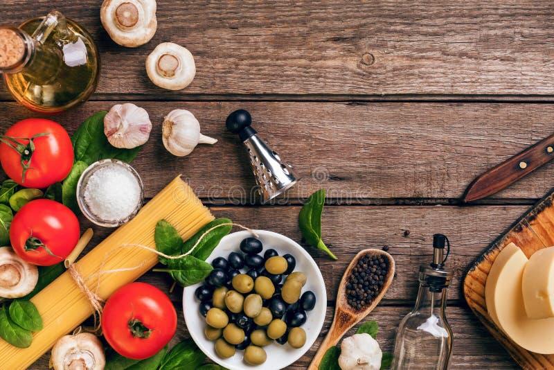 意大利面团、意粉、蓬蒿、蕃茄、橄榄和橄榄油的准备的未加工的成份在木 免版税图库摄影