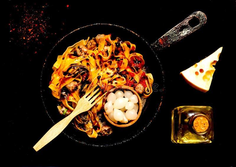意大利面团用丸子和烂醉如泥的葱在地道平底锅在黑暗的背景 普遍的美国意粉的概念 免版税库存图片