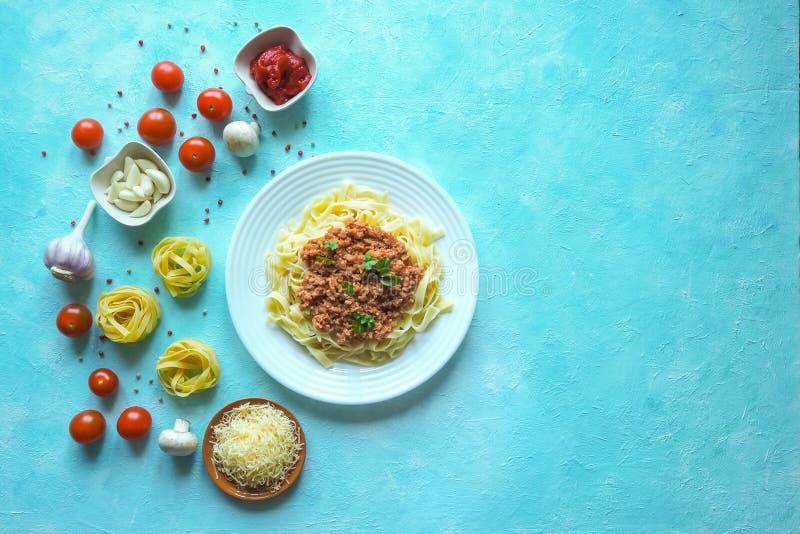 意大利面团用博洛涅塞调味汁 在蓝色桌上的菜 免版税库存照片