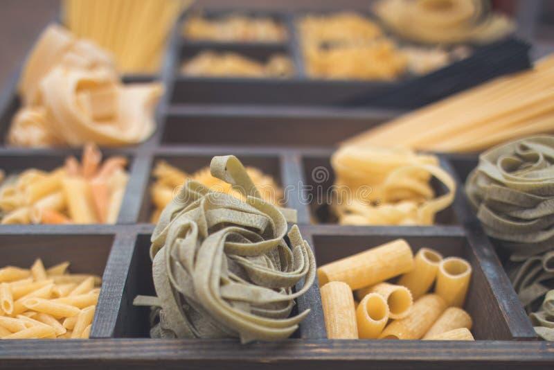 意大利面团的各种各样的类型在一个木箱的用不同的细胞 库存图片