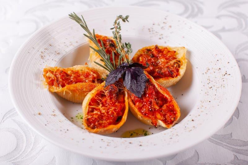 意大利面团Conchiglioni Rigati 可口盘充塞用绞肉用在西红柿酱的干蕃茄 特写镜头 免版税库存图片