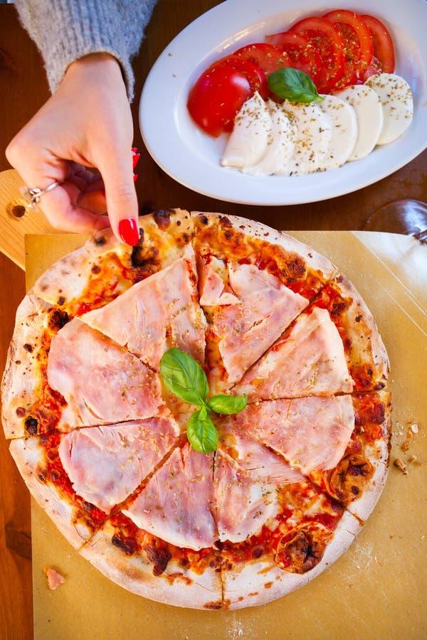意大利食物晚餐 吃与蕃茄熏火腿m的妇女薄饼 免版税库存照片