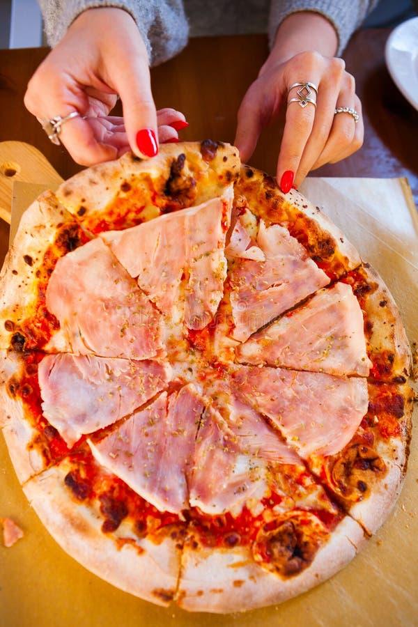 意大利食物晚餐 吃与蕃茄熏火腿m的妇女薄饼 免版税库存图片