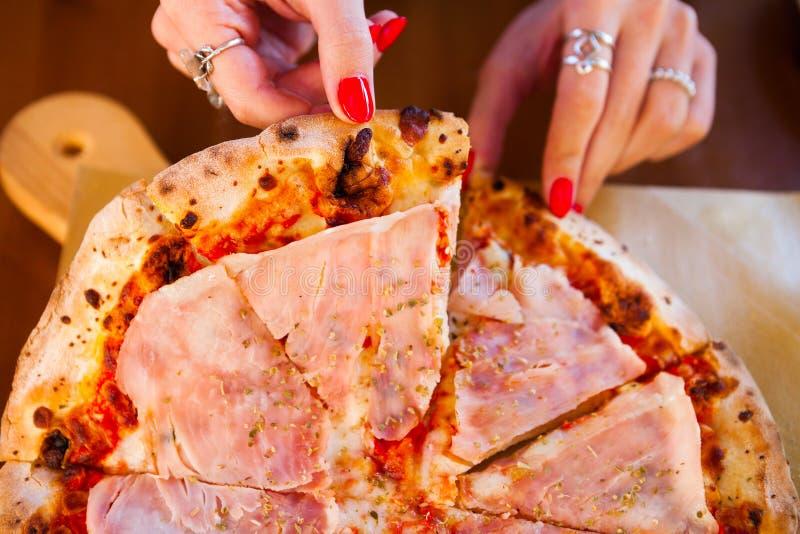 意大利食物晚餐 吃与蕃茄熏火腿m的妇女薄饼 库存照片