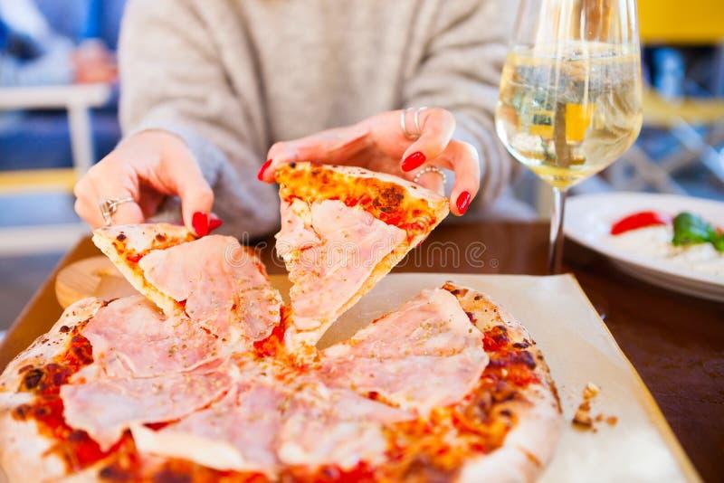意大利食物晚餐 吃与蕃茄熏火腿m的妇女薄饼 库存图片