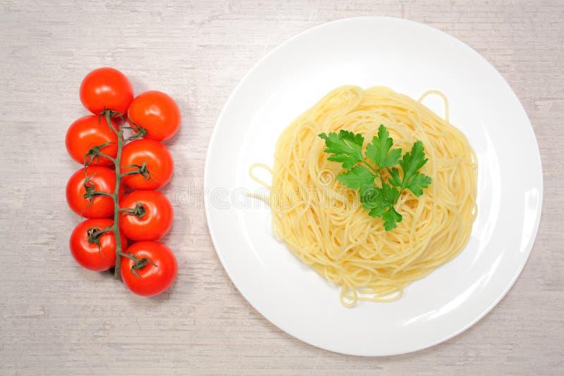 意大利食物:在一块大白色板材的面团在红色西红柿和绿橄榄旁边 免版税图库摄影