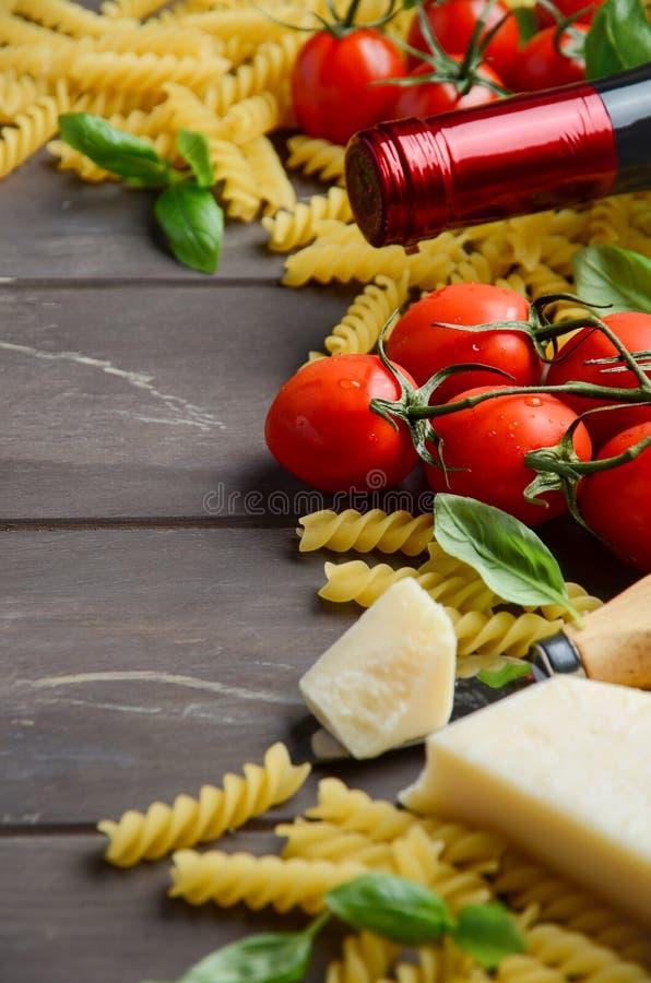 意大利食物-未加工的fusilli、蕃茄、蓬蒿、乳酪和酒在木桌上 库存图片