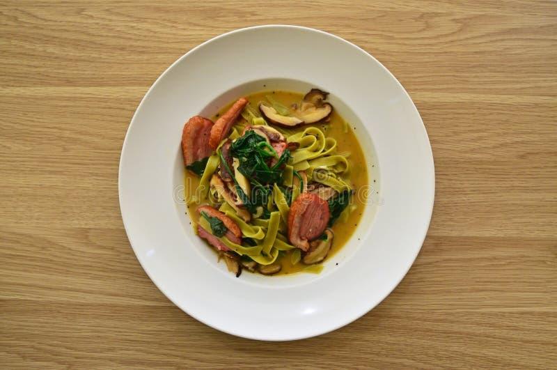 意大利细面条面团以鲜美汤新绿色枯萎了菠菜和切片熏制的鸭子 免版税库存照片