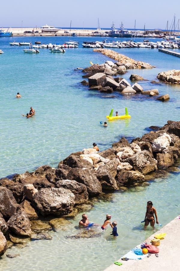 意大利otranto 与岩石、港口、小船和人的爱奥尼亚海在度假 免版税库存图片