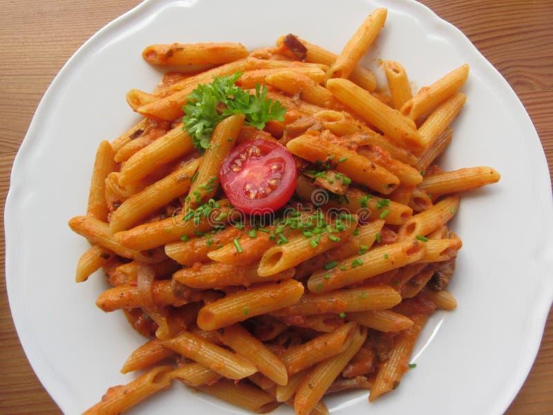 意大利penne面团用西红柿酱、奶油、蘑菇、烟肉和香葱 在视图之上 免版税库存图片