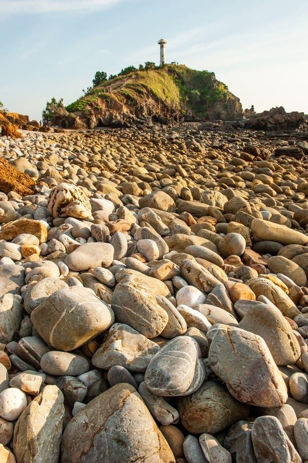 意想不到的在日落的风景石海滩,山灯塔弄脏了背景 朗塔海岛,泰国 免版税库存照片