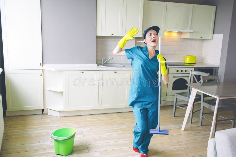 意想不到的妇女在厨房里站立,并且举行在手上擦 她挥动用手和大声唱歌  擦净剂有休息 库存图片