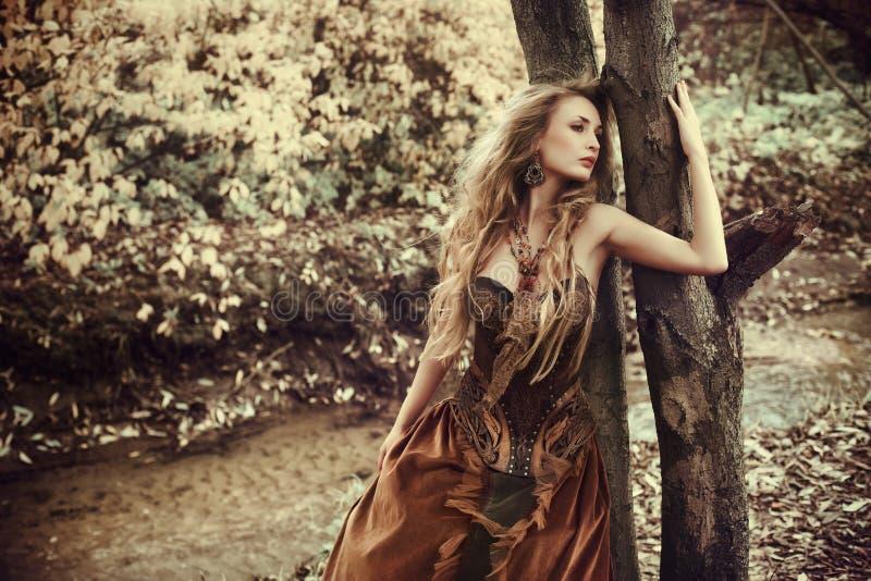 意想不到的妇女在秋天森林里 免版税库存图片
