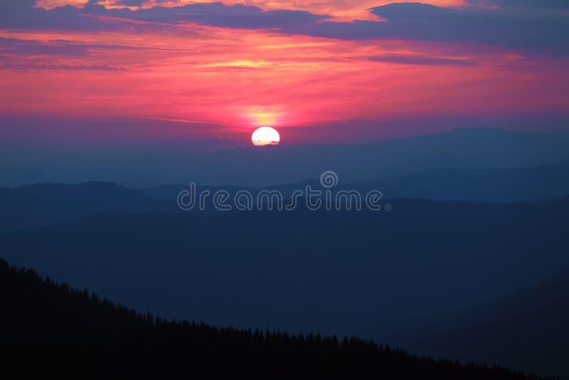 意想不到的日落启迪与奇妙颜色的天空:明亮的桃红色,黄色,橙色 山的风景 免版税库存图片