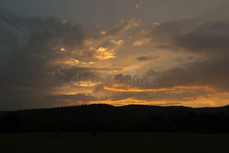 意想不到的红色日落和黑暗不祥的云彩 库存照片