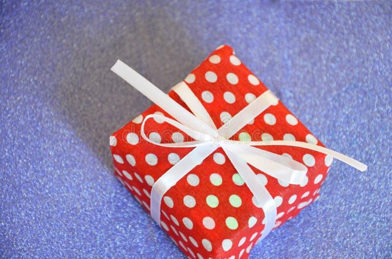意想不到的被包裹的当前红色包装平的位置在白色豌豆的与用在发光的闪耀的蓝色backg的弓装饰的白色丝带 免版税图库摄影