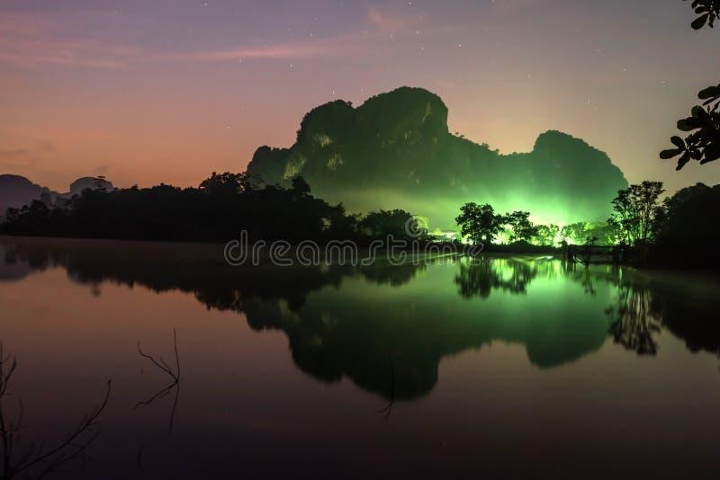 意想不到的风景湖和山夜有满天星斗的背景 点燃在山前面的村庄 日出 库存图片