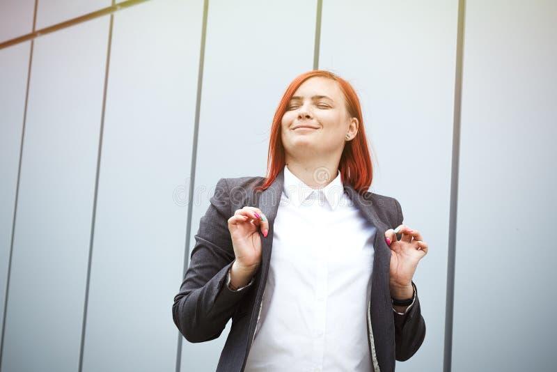 满意的成功的红发女孩上司,女实业家在su 免版税库存图片