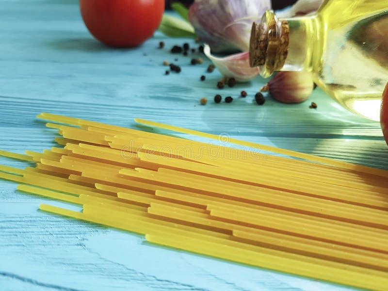 意粉上油健康食物preparatio晚餐,在木的蓝色的大蒜蕃茄黑胡椒 库存照片