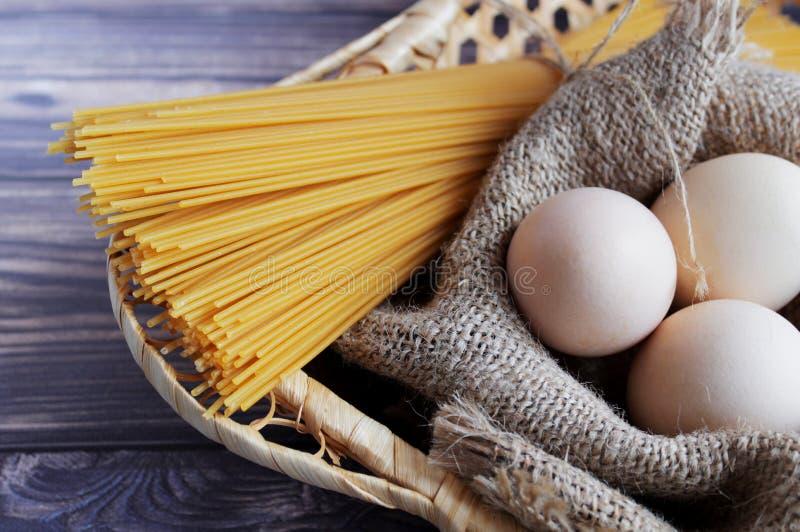 意粉和鸡蛋在一个黑暗的背景和竹篮子 免版税库存照片