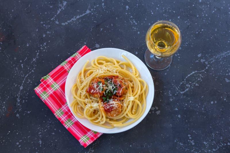 意粉用丸子、西红柿酱和帕尔马干酪在一块白色板材在黑暗的背景 库存照片