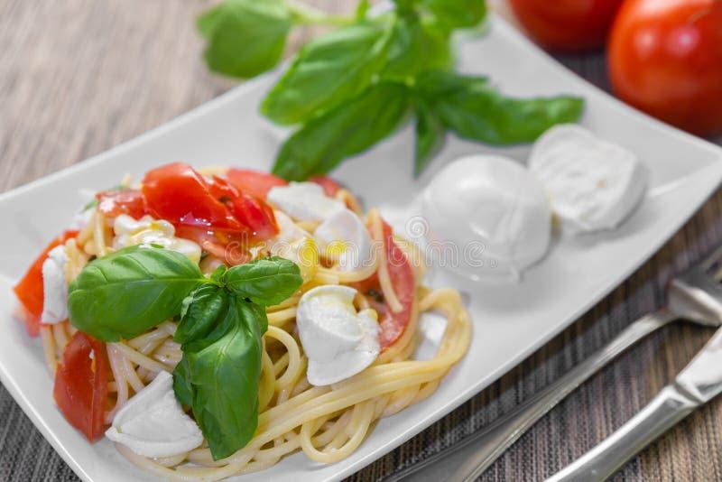 意粉用新鲜的蕃茄、蓬蒿和无盐干酪 库存照片