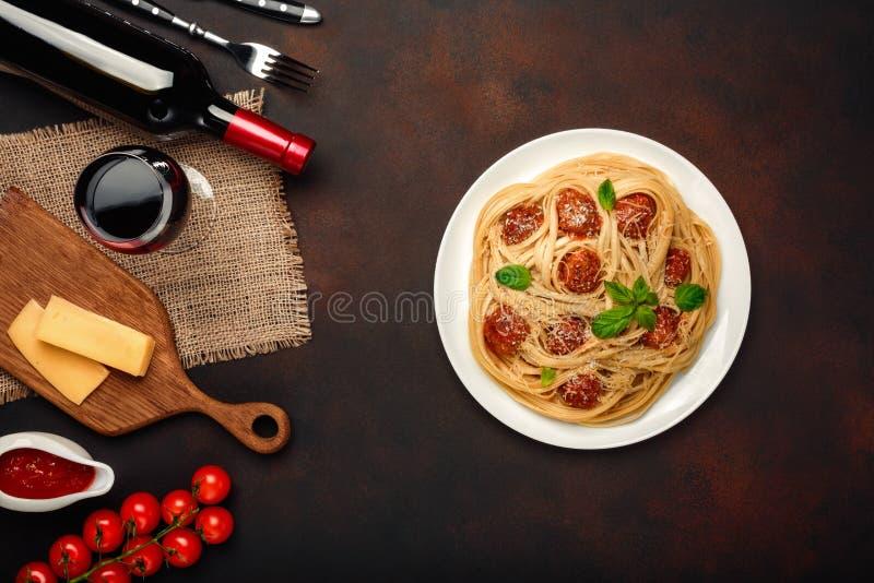 意粉面团用丸子,乳酪、西红柿调味汁、葡萄酒杯和瓶在生锈的背景喝酒 免版税库存照片