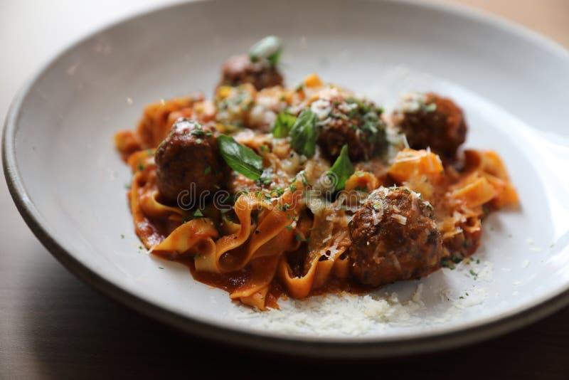 意粉面团用牛肉丸子和西红柿酱在板材,意大利料理 免版税库存图片