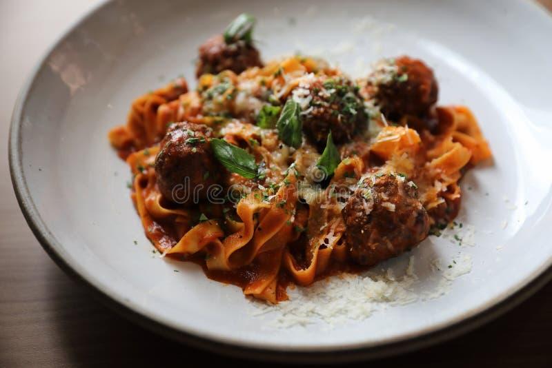 意粉面团用牛肉丸子和西红柿酱在盘,意大利料理 免版税库存照片