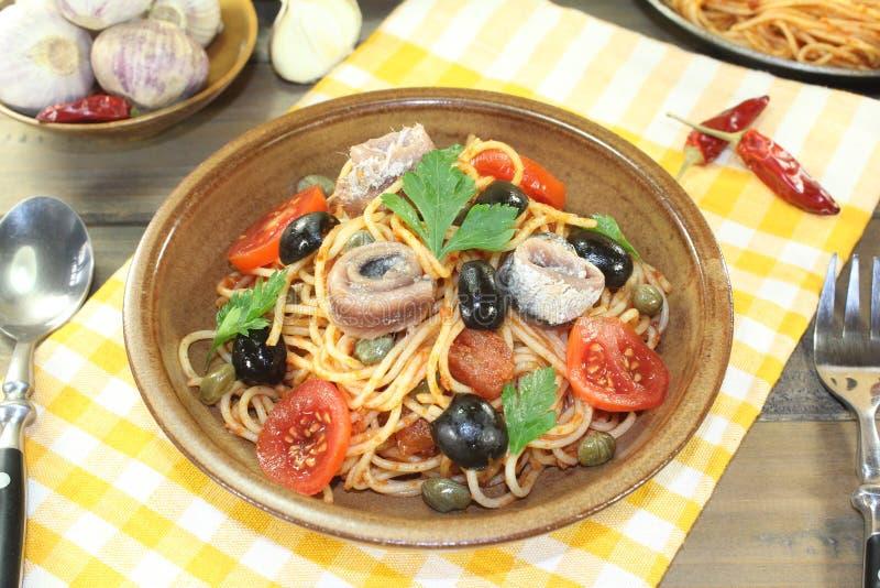意粉alla puttanesca用橄榄、雀跃和鲥鱼 库存照片