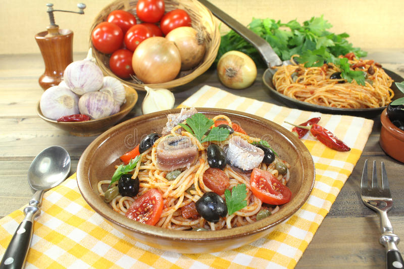 意粉alla puttanesca用雀跃和蕃茄 免版税库存图片