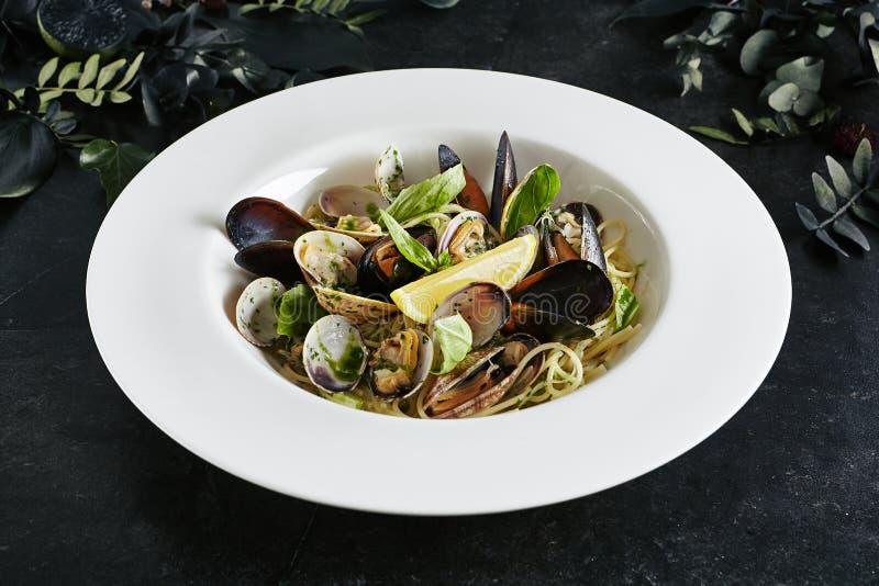 意粉Nido精妙的服务的白色餐馆板材有海壳的在酒酱汁 免版税库存图片