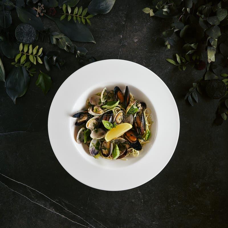 意粉Nido精妙的服务的白色餐馆板材有海壳的在酒酱汁 图库摄影
