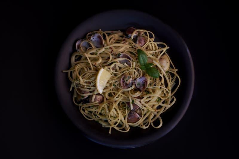 意粉vongole、意大利海鲜面团与蛤蜊和淡菜,在板材有草本黑背景 传统意大利海 免版税库存图片