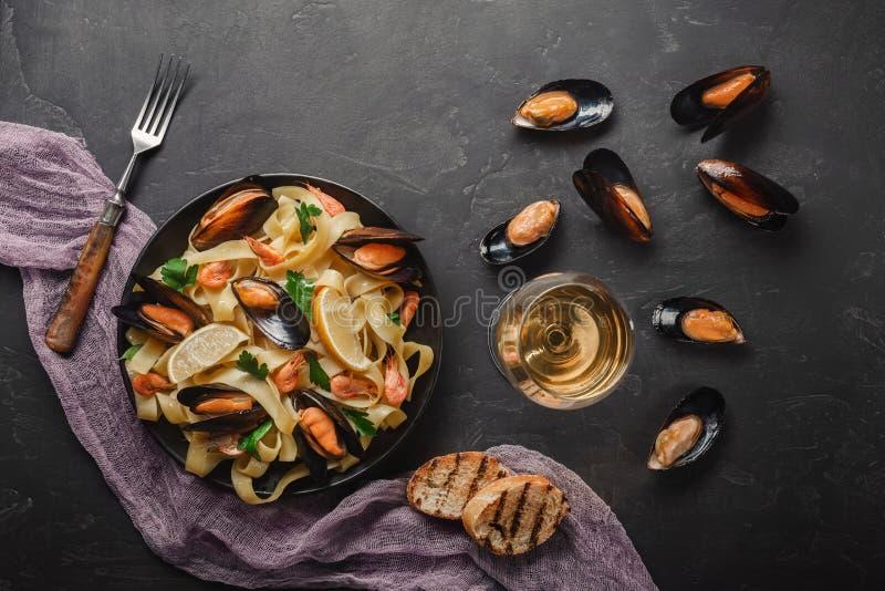 意粉vongole、意大利海鲜面团与蛤蜊和淡菜,在板材用草本和杯白酒在土气石头 免版税库存照片